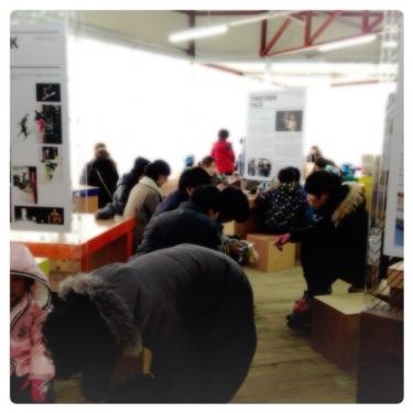 小さな写真ギャラリーの中で休憩や軽食をする人達。