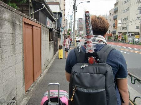 日本刀のお土産を背にしたアジア系の男性