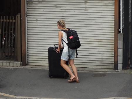 スーツケースを押す外国人女性の姿