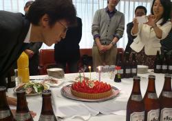 サプライズのお祝いケーキのろうそくを吹き消す中野社長