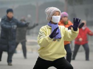 2013-01-30_China_中国の有害濃霧、日本面積の3倍に 病院取材を制限01_有害物質含んだ濃霧のため、北京市内の公園でマスクをしながら太極拳をする人たち=29日(共同)
