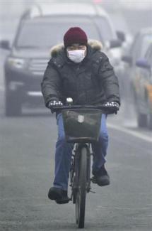 2013-01-30_China_中国の有害濃霧、日本面積の3倍に 病院取材を制限02_有害物質を含んだ濃霧のため、マスクをしながら自転車に乗る男性=29日、北京市内(共同)