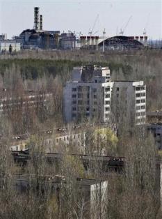 2013-04-27_Russia_Ukraine_チェルノブイリ原発事故から27年 原発推進の中核地に01_チェルノブイリ原発(奥)と、住民が避難して廃墟と化したプリピャチの町=23日(AP)