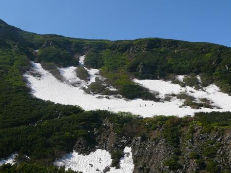 遠くに雪渓をトラバースする姿が見える