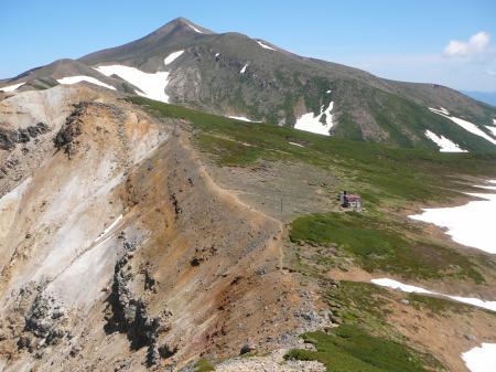 急斜面下に上ホロ避難小屋と奥に目指す十勝岳