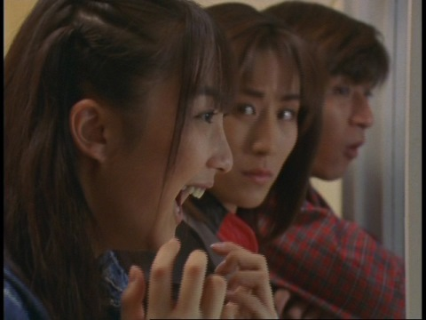 はしゃぐマイ隊員に一抹の不安を感じるユミムラ・リョウ隊員(演:斉藤りさ)
