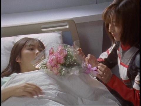 シオンからの花束と言って、マイ隊員に渡すユミムラ・リョウ隊員(演:斉藤りさ)