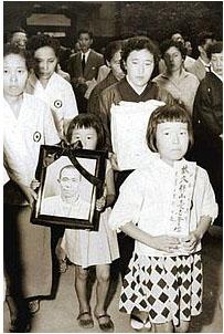 blog 亡くなった久保山さんの遺影と遺骨を手に歩く妻と娘ら