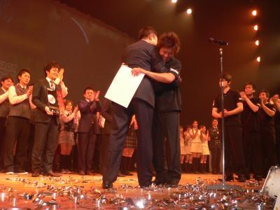 第2回の決勝大会で日本一となって木山理事長と抱き合う「JOY STAGE」グループの趙常務