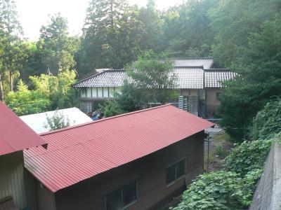 山に囲まれるように佇むK山の家。トイレ小屋は一番奥にあって見えない