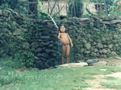 手作りシャワーで水浴びを楽しむ開放的なネパール少女
